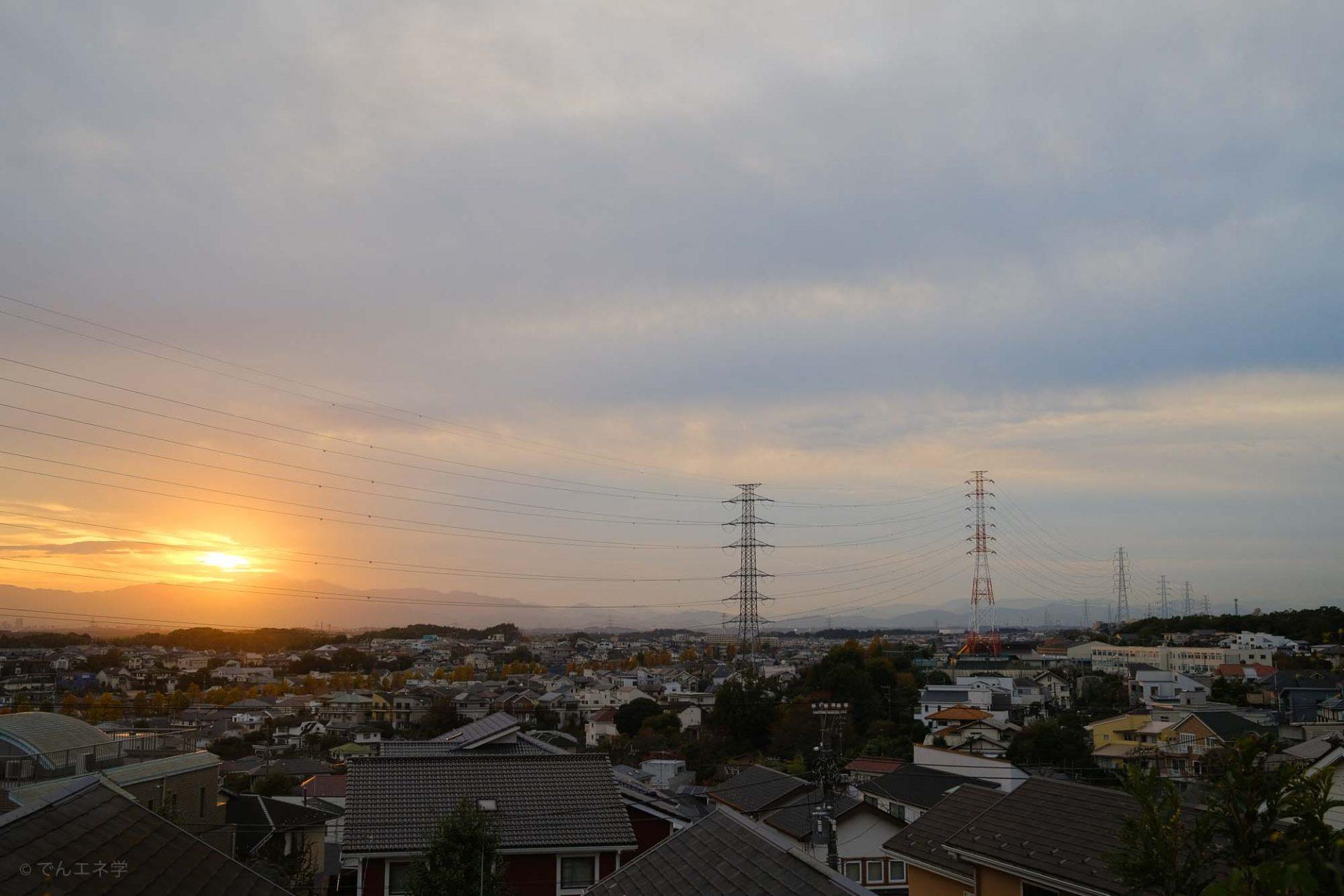 住宅街と高い鉄塔、太陽
